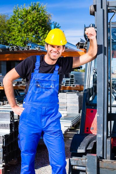 Builder with site pallet transporter or lift fork truck Stock photo © Kzenon