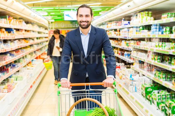 Man with shopping cart in hypermarket Stock photo © Kzenon