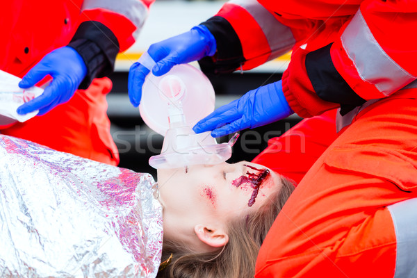Ambulance doctor giving oxygen to female victim Stock photo © Kzenon
