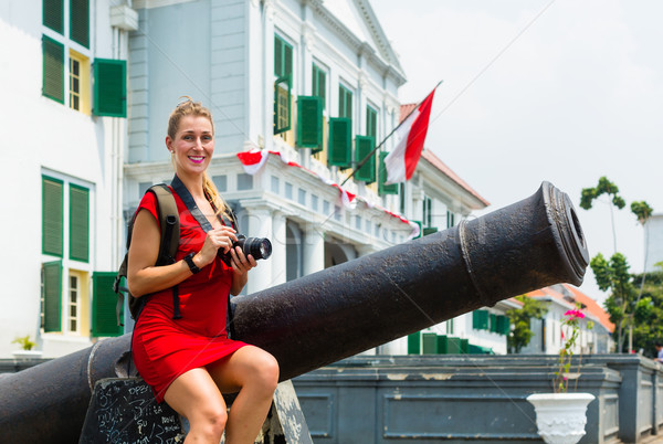 Stock photo: Tourist sitting on cannon in old Batavia Jakarta Indonesia