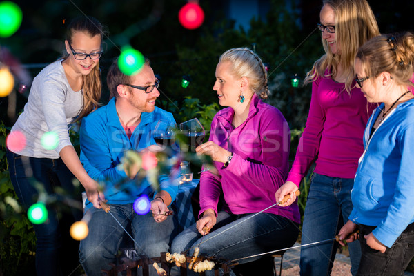 Family grilling bread on a stick at barbeque Stock photo © Kzenon