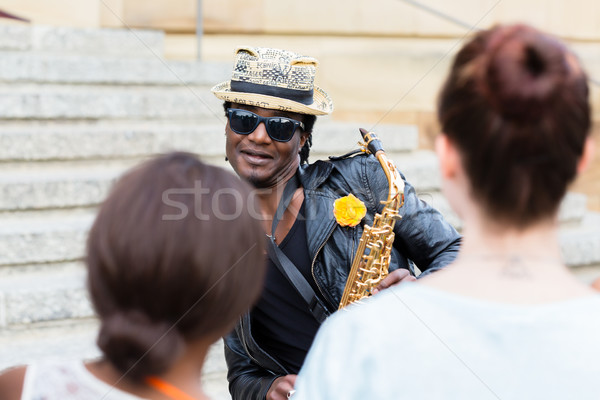 Black Street musician with sunglasses and saxophone making music Stock photo © Kzenon