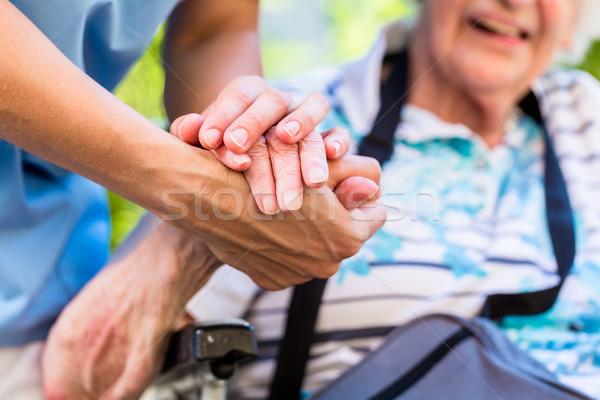 Nurse consoling senior woman holding her hand Stock photo © Kzenon