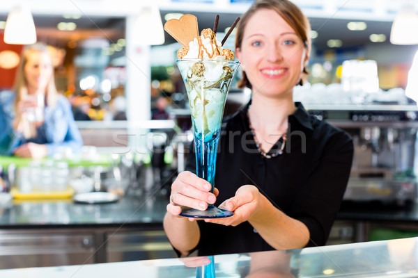 Saleswoman in ice cream parlor presenting sundae Stock photo © Kzenon