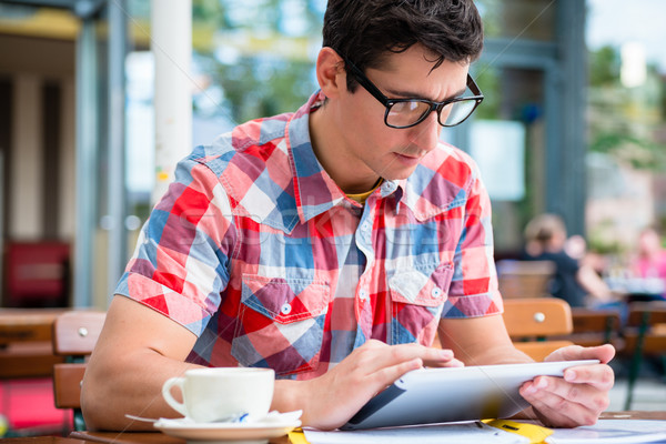 Man drinking coffee in street cafe reading on tablet device Stock photo © Kzenon