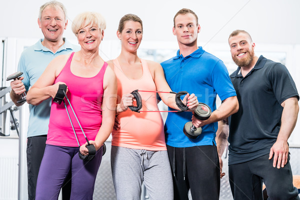 Group of people in gym with stretch bands and dumbbells Stock photo © Kzenon