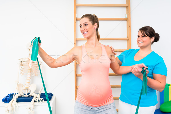 Pregnant woman exercising with resistance band in physiotherapy Stock photo © Kzenon