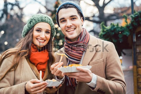Woman and man eating and drinking on Christmas market Stock photo © Kzenon