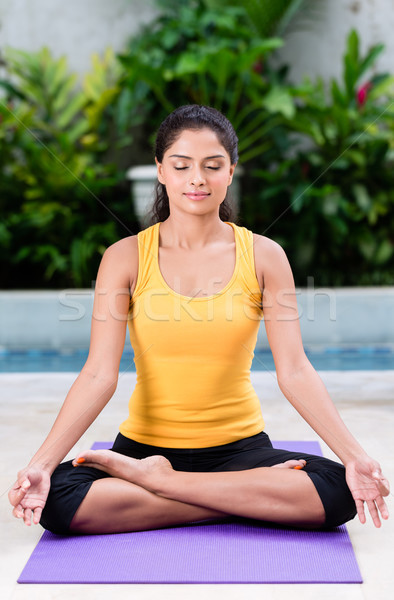 Serene young woman sitting in lotus position outdoors Stock photo © Kzenon