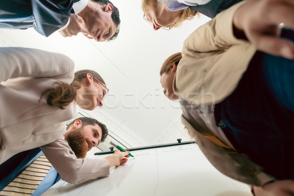 Low-angle view of an international team working together during  Stock photo © Kzenon