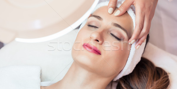 Relaxed woman smiling under the benefits of anti-aging facial ma Stock photo © Kzenon