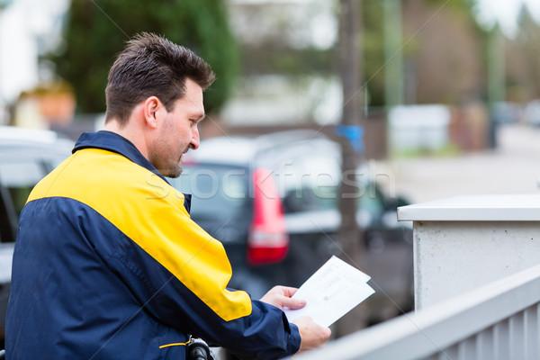 Postman delivering letters to mailbox of recipient Stock photo © Kzenon