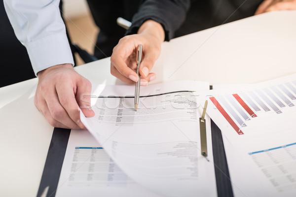 Business man and woman analyzing financial reports Stock photo © Kzenon