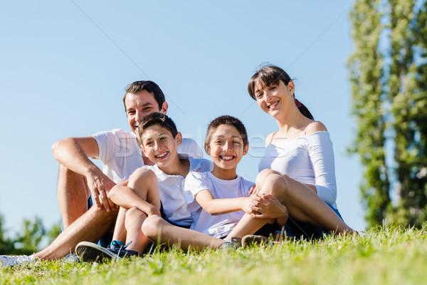 Family dressed in white in park in summer sitting in meadow Stock photo © Kzenon