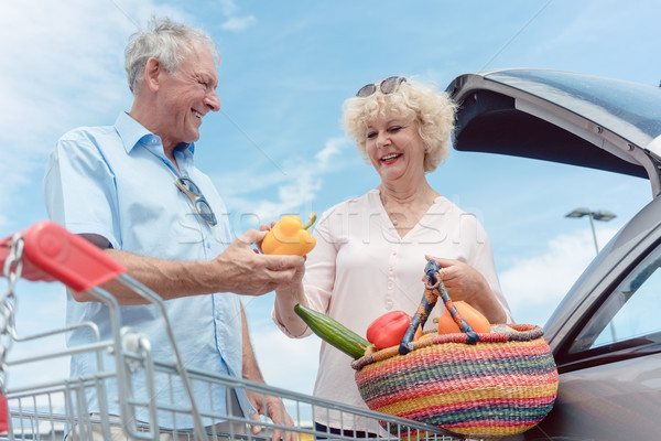 Cheerful senior couple happy for buying fresh vegetables from the hypermarket Stock photo © Kzenon