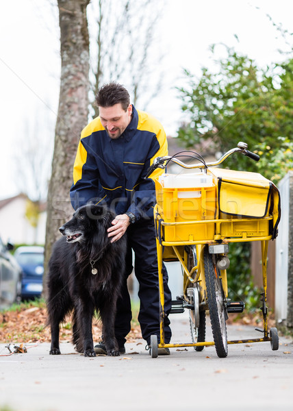 Big black dog welcoming postman at garden gate Stock photo © Kzenon