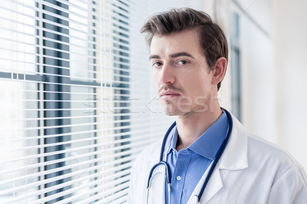 Portrait of a young serious doctor looking at camera with determination Stock photo © Kzenon