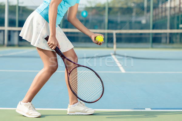 Low section of a young woman wearing white skirt and tennis shoe Stock photo © Kzenon