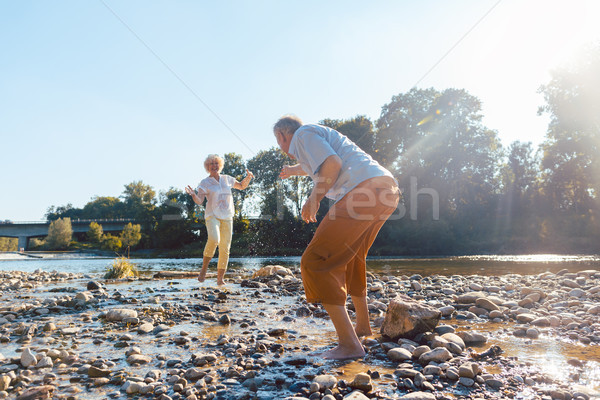 Funny senior couple playing with water at the river in a sunny day Stock photo © Kzenon