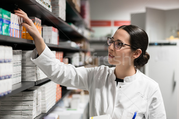Dedicated pharmacist taking a medicine from the shelf during work Stock photo © Kzenon
