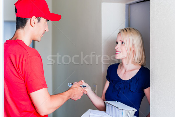 Delivery man taking payment from female customer Stock photo © Kzenon