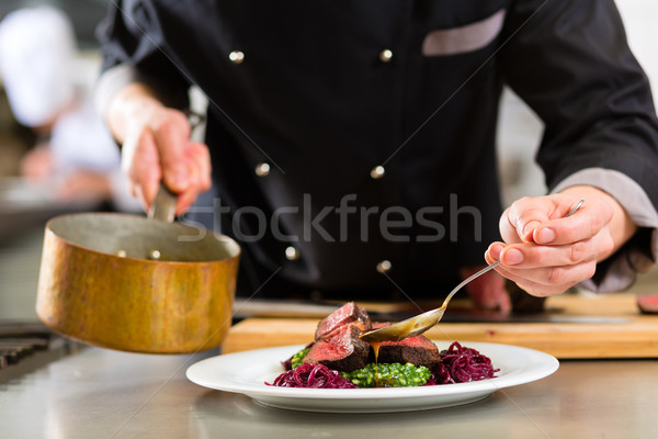 Chef in hotel or restaurant kitchen cooking Stock photo © Kzenon