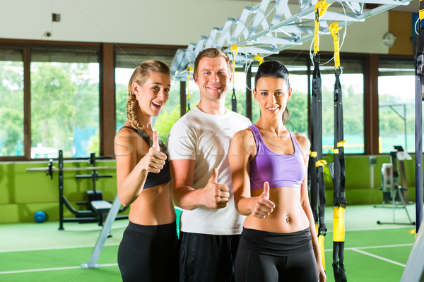 People in sport gym on suspension trainer Stock photo © Kzenon