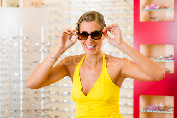 Young woman at optician with sunglasses Stock photo © Kzenon