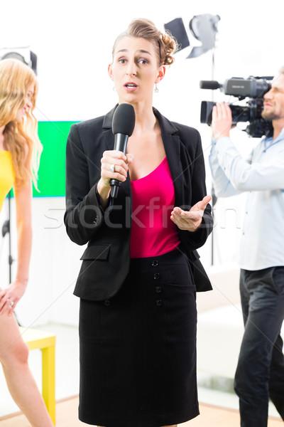 Reporter moderating an interview on film set Stock photo © Kzenon