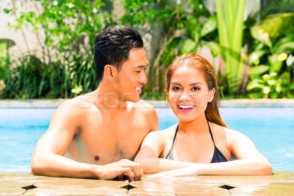 Asian couple swimming in resort pool Stock photo © Kzenon