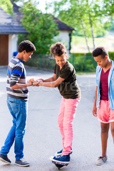 Three kids playing together with board Stock photo © Kzenon