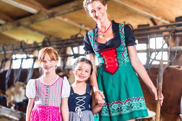 Bavarian mother showing children cows in cow farm Stock photo © Kzenon