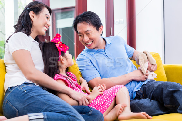 Chinese Family playing with daughter on sofa Stock photo © Kzenon