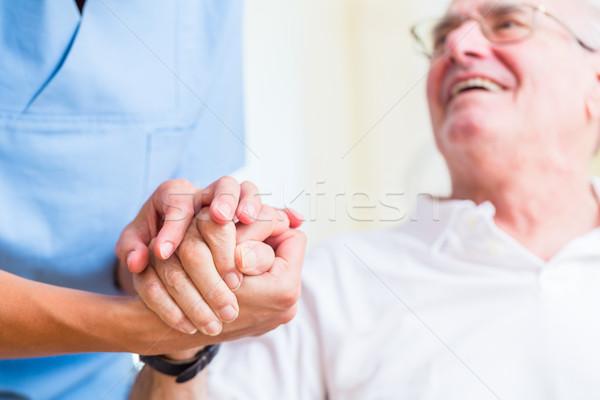Nurse holding hand of senior man in rest home Stock photo © Kzenon