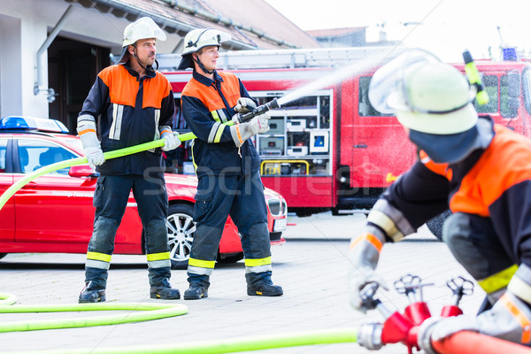 Stock photo: Fire fighter connecting hoses
