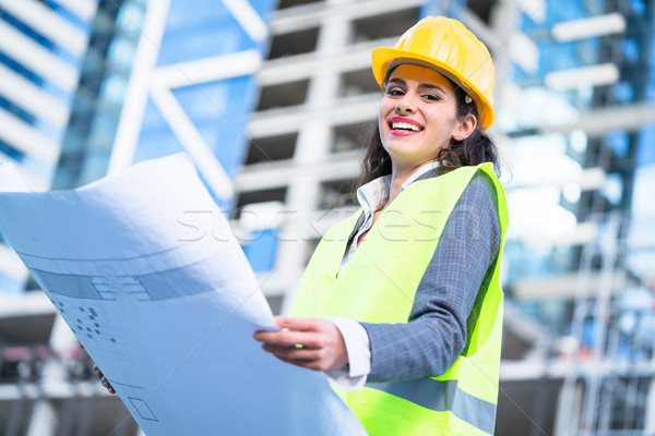 Female civil engineer studying drafts visiting construction site Stock photo © Kzenon