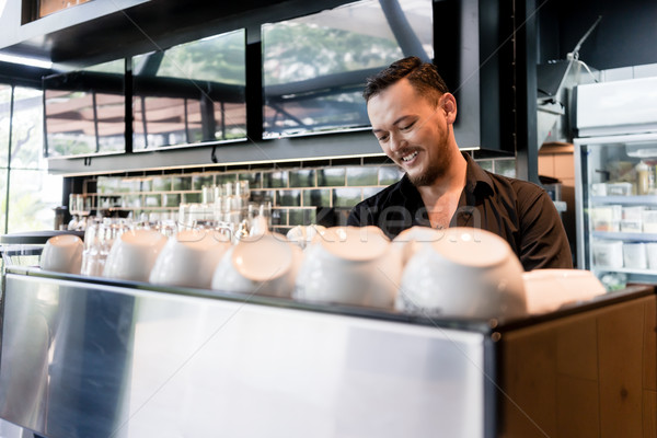 Happy young man working as barista behind the bar counter of a m Stock photo © Kzenon