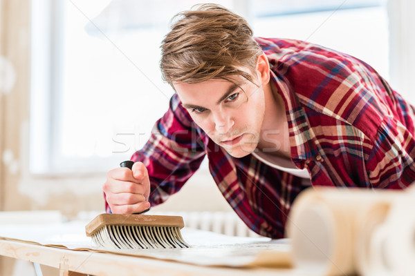 Young man applying paste to the surface of a wallpaper sheet dur Stock photo © Kzenon