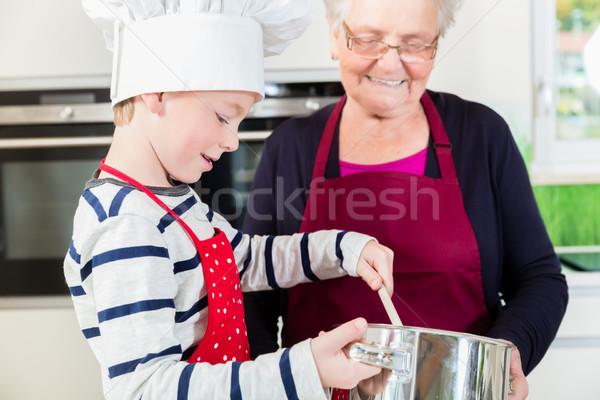 Granny and little boy preparing food in kitchen Stock photo © Kzenon