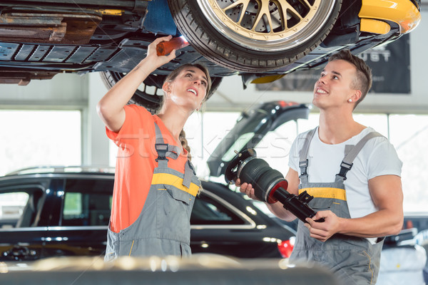 Experienced female auto mechanic installing a new air suspension system Stock photo © Kzenon