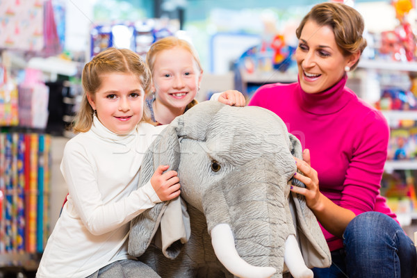 Family in toy store cuddling with stuffed animal Stock photo © Kzenon