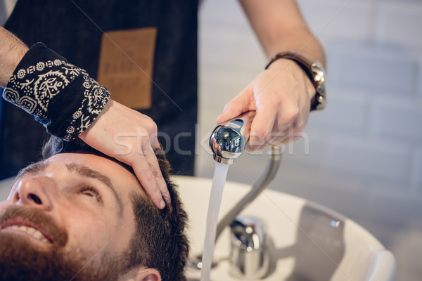 Close-up of the hands of a skilled hairdresser giving a hair wash Stock photo © Kzenon