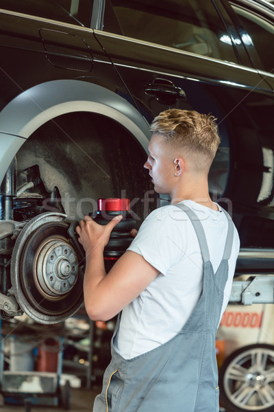Experienced mechanic replacing the disk brakes of a car in a modern repair shop Stock photo © Kzenon