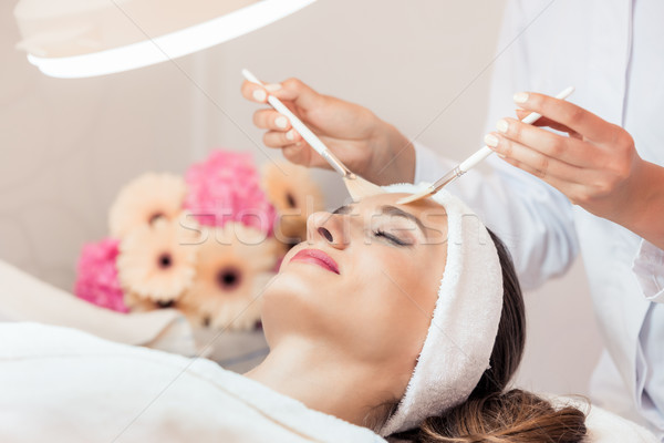 Beautiful woman during anti-aging facial massage in a modern center Stock photo © Kzenon