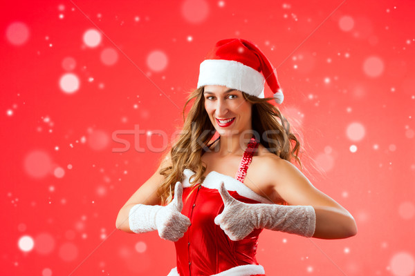 Attractive young woman in Santa Claus costume with thumbs up Stock photo © Kzenon