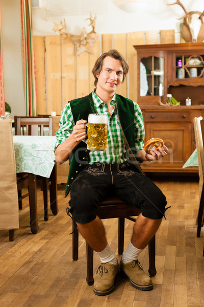 Young man in traditional Bavarian Tracht in restaurant or pub Stock photo © Kzenon