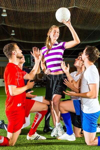 Woman has a football in hand, men kneeling down Stock photo © Kzenon