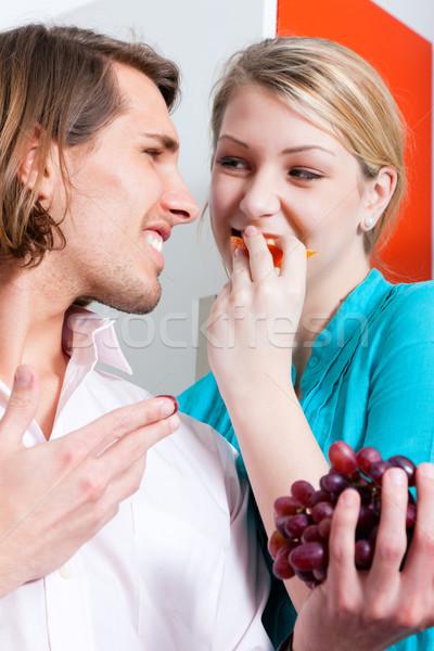 Couple eating grapes at home Stock photo © Kzenon