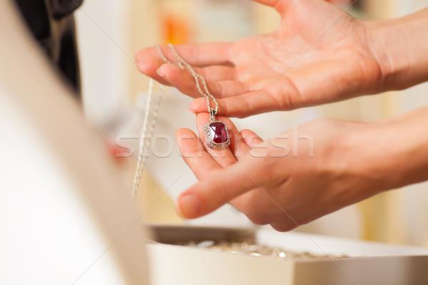 Female jeweller presenting jewellery Stock photo © Kzenon