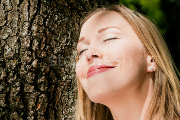 Girl cuddling a tree and dreaming Stock photo © Kzenon